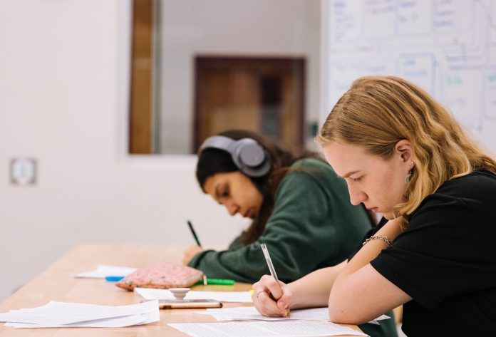 girl in black t-shirt writing on white paper