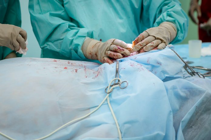 person in operation gown holding scissors