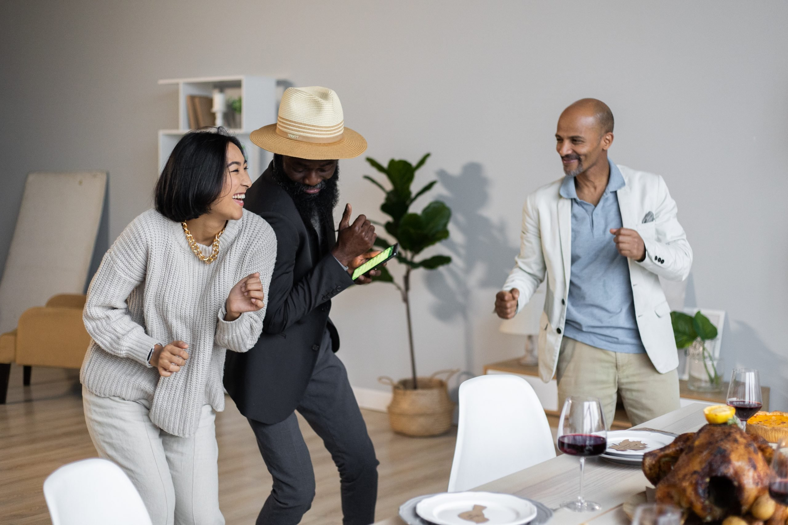 Positive diverse friends dancing while celebrating thanksgiving