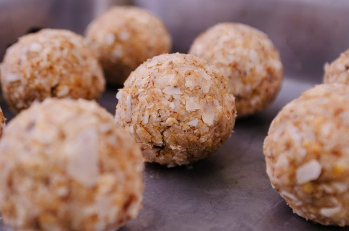 Uncooked round meatballs on metal tray