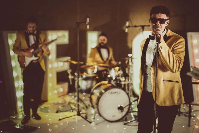 24K Motown & Soul Band singing and performing live for a new video, wearing gold jackets and tinted sunglasses - bringing style and class to the lit dancefloor.