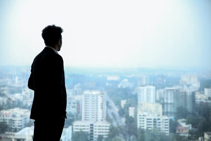 High AmbitionMan in Black Suit Standing on Top of Building Looking At City Buildings