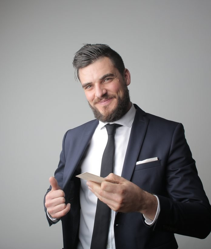 Man in black suit holding a calling card