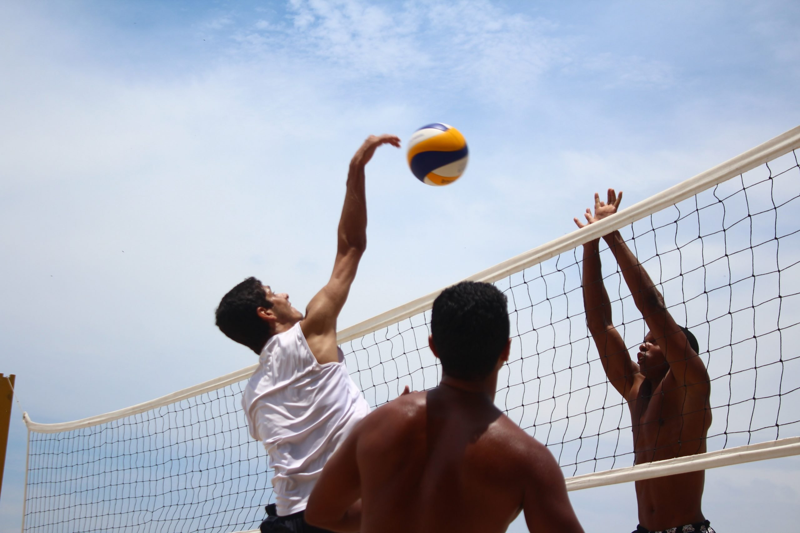 man in white shorts playing volleyball during daytime