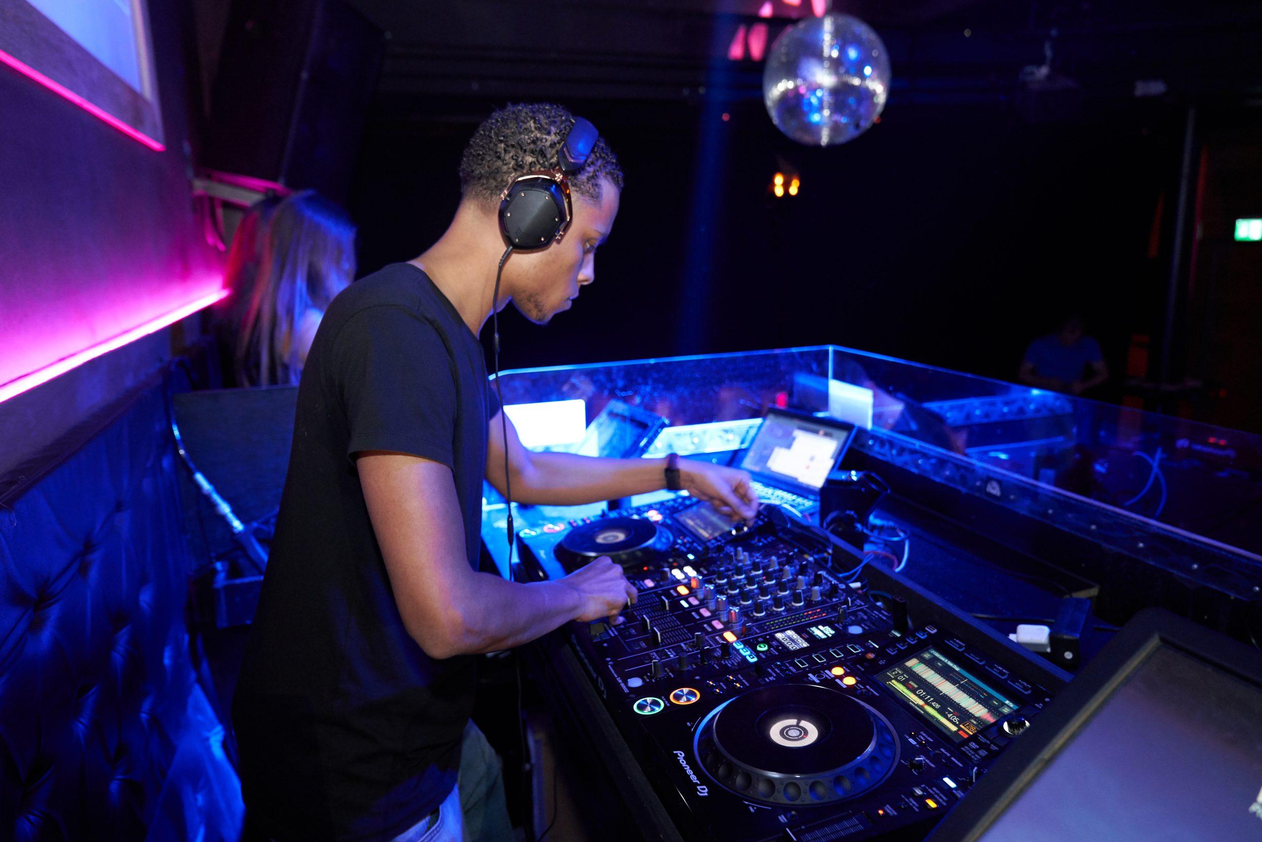 Man wearing black crew neck shirt playing dj turntable