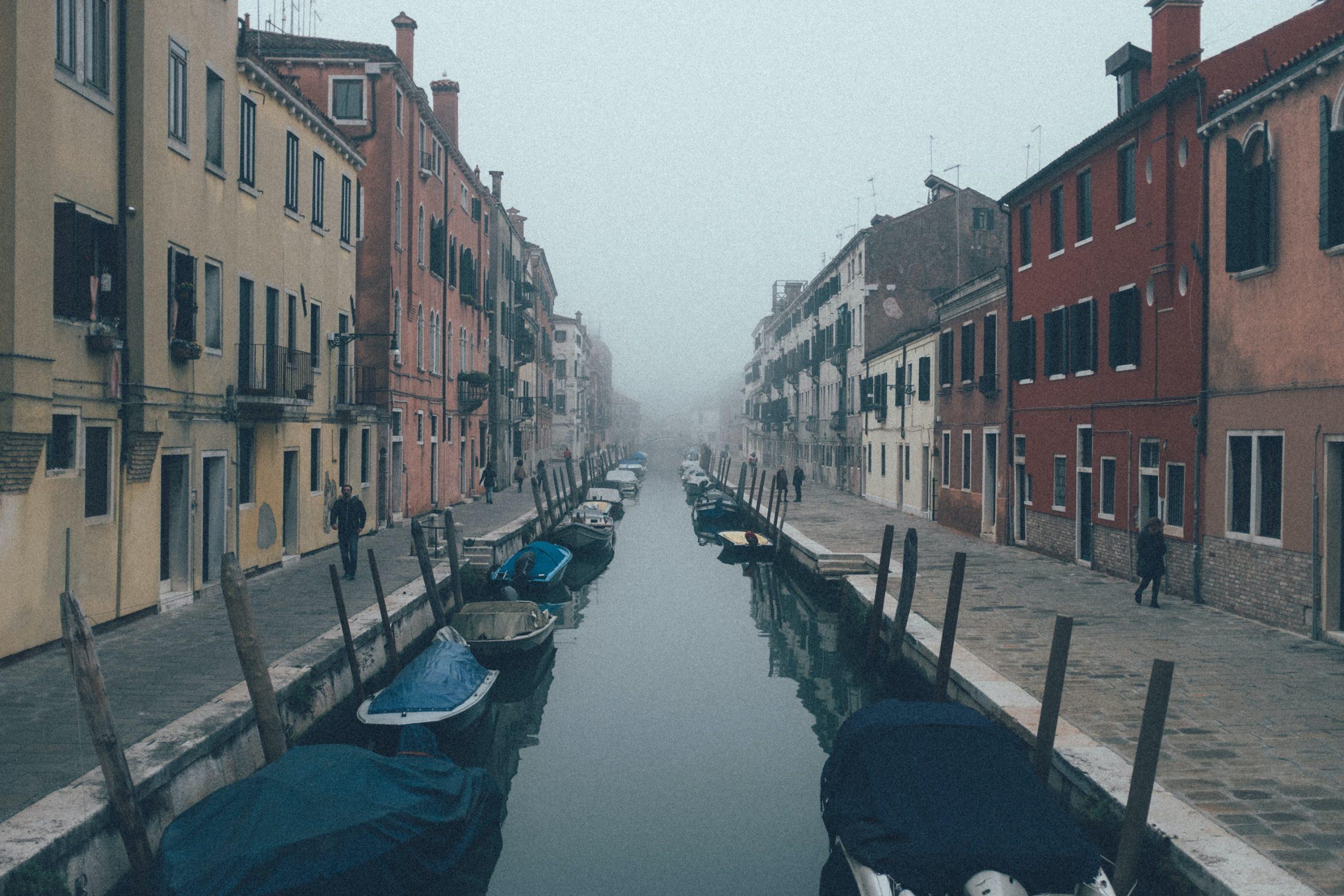 person standing beside water between houses