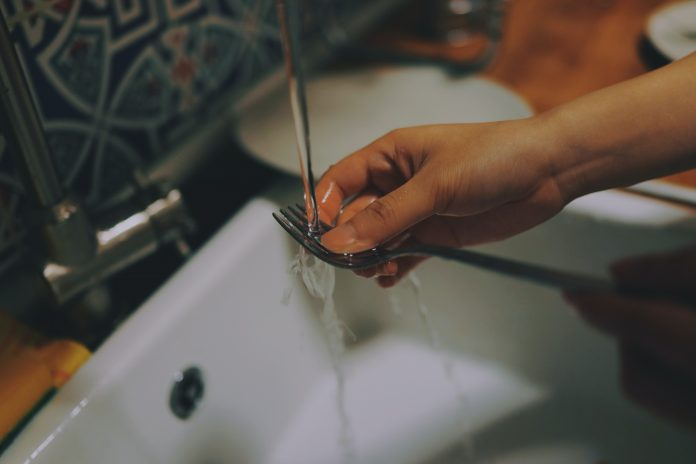 person washing fork