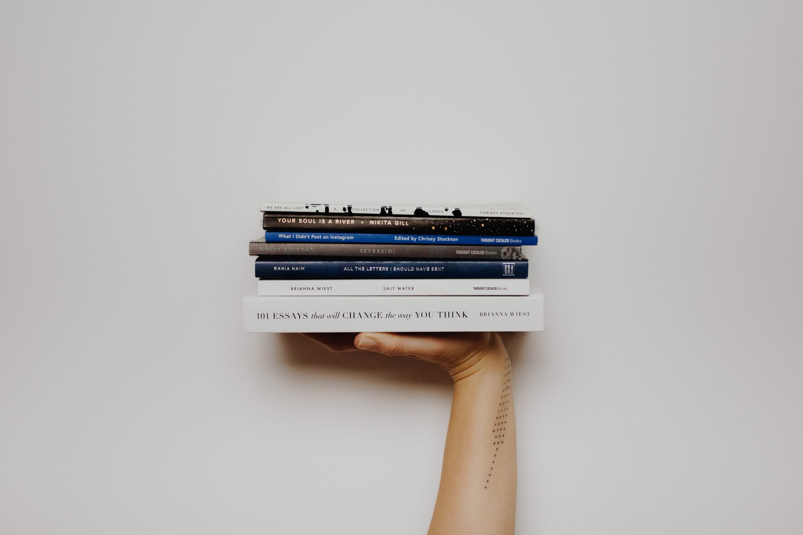 Woman with a tattoo holding up a stack of books.